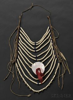 Northern Plains Loop Necklace | c. last quarter 19th century | With eleven strands of shell beads strung between strips of commercial leather accented by large dark blue glass beads, brass shoe buttons, and a large shell disc, lg. 19 in. | 1000$ ~ Sold