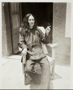 "Frida Kahlo after an operation, 1946, by Antonio Kahlo. The lingering pain from her Sept. 1, 1925, bus accident led to a series of operations throughout her life. Though she often dressed up in colorful traditional Mexican patterns and jewelry, with her hair up, she appears in this small image, taken by her nephew, looking quite different in monochrome pajamas and her hair down. On the rear of the photo is written: ""Frida right after surgery in 1946 — Coyoacan — she is now worse than ever."