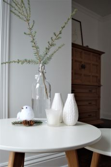 Scandinavian style nesting tables are perfect in any room, mixed with modern or traditional furniture. All white Christmas decor with greenery branches; heirloom linen closet; wooden furniture; minimalist Nordic Christmas decor.