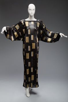 Evening gown, Gianni Versace, 1986. Black chain mail with gold and silver geometric design, inspired by painter Gustav Klimt.