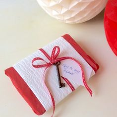If you're wrapping something awkward like lingerie or a tie, wrap it in some tissue and add a strip of thick paper to keep the shape. Here i've added some Narrow red ribbon and a tag to decorate