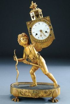 "A FRENCH EMPIRE GILT-BRONZE FIGURAL MANTLE CLOCK circa 1810, finely cast and chiseled figure of cupid with enameled eyes holding a bow, wearing a quiver, and supporting a clock case upon his wings. Some losses. Height 18""."