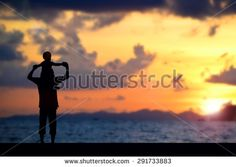 Father day ,father and son silhouettes play at sunset beach blurred background - stock photo