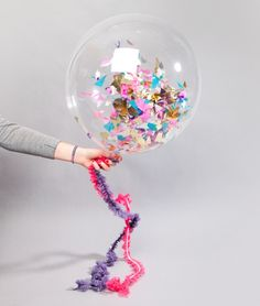 Fill clear balloons with confetti or glitter! For an extra added touch to your balloons, consider using other string options as opposed to party ribbon. Or, you can decorate your ribbon with small pieces of paper, mini pompoms, or anything else that won't weight it down too much