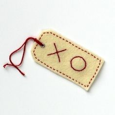 Pattern and tutorial for making embroidered felt gift tags that look like standard issue manila shipping tags.