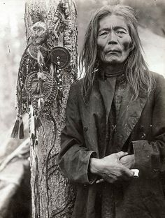 Evenk (Russian minority) shaman with a collection of shamanic objects, including images of helper spirits, early 1900s.