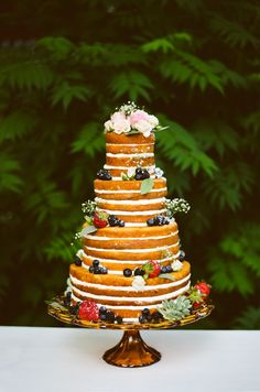 Made by pastry chef Greg Marsh, the couple's four-tiered naked cake was in keeping with the Arcadian theme. It sat on an amber glass pedestal, enwreathed in sugar-dusted berries and accented with tiny sprigs of baby's breath. | Photo by E + E Photography