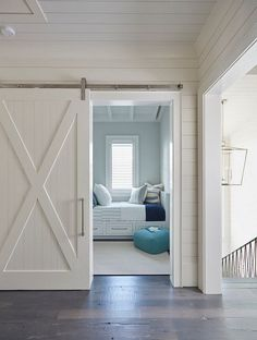 This white shiplap barn door opens to reveal a kids' bedroom filled with white built-in beds with storage drawers.