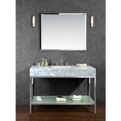 This vanity set features an open-back industrial design with a polished stainless steel base and versatile white carrera marble countertop with built-in sink. Storage is provided through a frosted tempered glass shelf on the lower base.