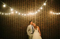 The bride rests her head on the groom's shoulder while they lean against brick wall underneath globe string lights at their wedding reception.