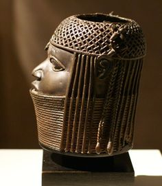 A carved ivory tusk was placed in the opening of this bronze head. From Benin, Nigeria