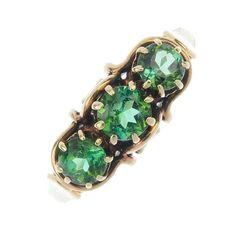 A diopside three-stone ring designed as a graduated green diopside line, to the openwork gallery and grooved band.  This is a perfect statement