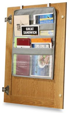 """Over-The-Cabinet-Door Coupon Pockets / Price: $7.99 / Everyone has a """"junk drawer"""" in the home somewhere — mine is in my kitchen. It's where flyers for new restaurants, take-out menus and appliance manuals go. This over-the-door pocket tucks away and puts these things at arm's reach and out of sight at the same time."""