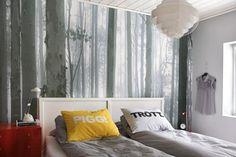 På soverommet har skogen fått plass ved sengen, i form av en tapet bestilt fra komar.de. Putene er fra Lagerhaus i Stockholm. Taklampen er kjøpt second-hand i Cape Town.