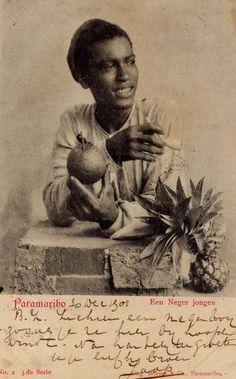 """Op deze prentbriefkaart zien we een jongeman met pijp. Hij houdt een sinasappel in zijn hand en naast hem zien we een ananas. Voor ons misschien vrij alledaagse zaken maar rond 1900 waren tabak en dergelijke exotische vruchten producten die rijkdom uitstraalden. Het onderschrift 'Een Neger Jongen' geeft aan de dat de maatschappij nog grotendeels werd ingedeeld op basis van kleur en etniciteit. De verzender van de ansichtkaart schrijft: """"B.Z. zie hier een negerboy zoals je ze hier bij hoopen…"""