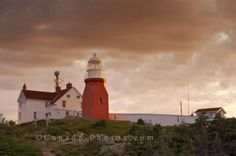 Picture of the Long Point Lighthouse in Twilligate in Newfoundland, Canada as the clouds block out the sunset hues.