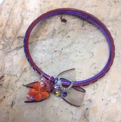 Ladies embellished double bangles.  Red and purple bangles embellished with beads, wire and a bow featuring an orange flower.  A16BAN04 by GoldRibbonsStudio on Etsy https://www.etsy.com/au/listing/275543322/ladies-embellished-double-bangles-red