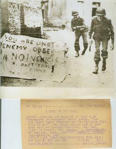 """""""Vous êtes sous observation de l'ennemi - pas de véhicules delà de ce point"""". Deux américains penchés dans leur déplacement passent une position exposée. De gauche à droite: le Pfc. Russell J. Schoonmaker, de Shelton, Connecticut et le Pvt. James V. Pappas, Indianapolis, Ind. July 13, 1944."""