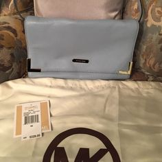 Michael Kors Beverly Clutch This is an awesome, oversized Michael Kors Beverly Clutch in pale blue with gold hardware. New with tags..never worn. It is in great condition inside and out. Comes with long strap so it can be worn as a cross body. Comes with original receipt, authenticity card, and dust bag. Michael Kors Bags Clutches & Wristlets