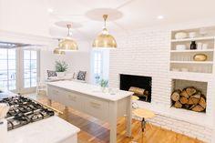White kitchen, open shelving, kitchen island, kitchen fireplace, brass, white brick. Design+styling by @pencilpco. Circa Lighting. Photo: Leslee Mitchell.