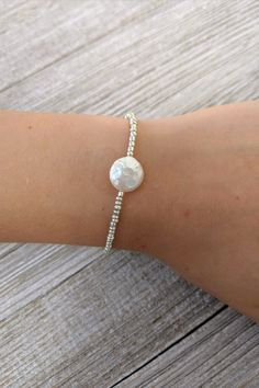 This beautiful delicate beaded bracelet is made with metallic silver glass seed beads and prominently features a single freshwater coin pearl. This bracelet looks great by itself or stacked with other bracelets! It would make a nice gift or it could be a great addition to your own jewelry collection! Get it today in the size you need. Custom size available. #caitlynclareflair #pearlbracelet #freshwaterpearl #beadedbracelet #silverbracelet #seedbeadbracelet #etsyjewelry #handmade #beautiful