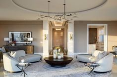 The curved furniture and rug, reflect the architectural ceiling element in this lovely living room.