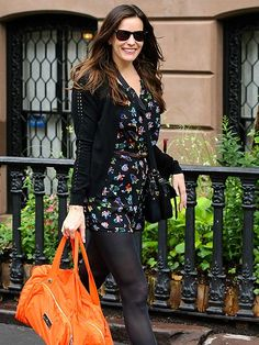 Liv Tyler, in classy rectangular wayfarers, added a pop of vibrant color to her otherwise all-black look with a citrus orange tote!