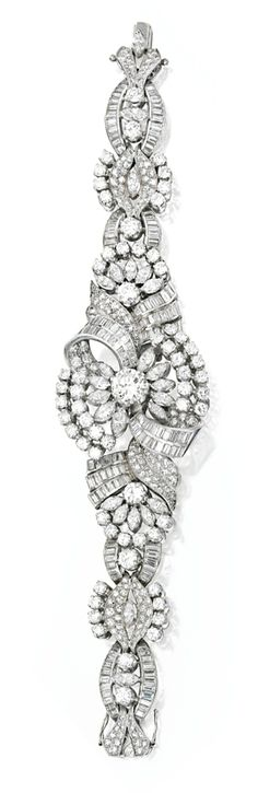 PLATINUM AND DIAMOND BRACELET, CIRCA 1950.  Centered by a round diamond weighing approximately 2.15 carats within scrollwork surrounds, further set with numerous round, baguette and marquise-shaped diamonds weighing approximately 24.70 carats, length 7 inches.