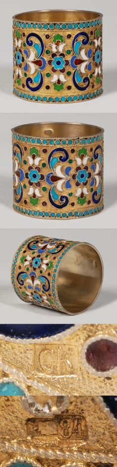 A RUssian silver gilt and cloisonne enamel ring by Simon Kazakov, Moscow, Circa 1908-1917. The oval ring decorated with scrolling floral and foliate motifs against a gilded stippled ground.