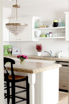 Me Oh My | white cabinets + open shelving + subway tile wall + gorgeous crystal chandelier