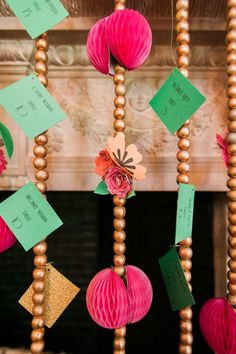Seating guide idea: green 'escort' cards hang from gold beads adorned with paper flowers at a Willowdale Estate summer wedding with creative and vibrant colors!