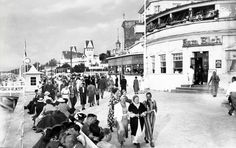 Das Hotel ''Zum Elch'' (rechts) war sehr angesagt, da es sich in der Mitte der Promenade befand, nicht weit von der ins Meer hinausfuehrenden hoelzernen Mole entfernt, auf der die Gaeste gerne spazieren gingen. Im Hintergrund (links) sieht man das mondaene Hotel Monopol. Ansichtskarte 30er Jahre, aus der Sammlung von André Gebler, Dresden.