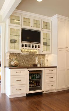 Amazing bar with gorgeous Arley brick mosaic backsplash. Leaded glass cabinetry doors. Built-in ice machine. Integrated bar refrigerator. General contracting by Martin Bros. Contracting, Inc.; kitchen by Hoosier House Furnishings, Inc.; interior design by Sandy Plummer, SP Interiors; photos by Marie Kinney Photography. www.MartinBrosContracting.com