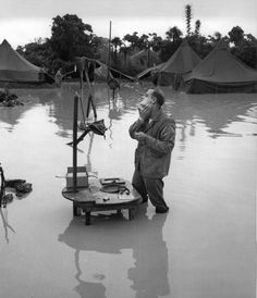 U.S. Marine Corps Staff SergeantA. S. Barnacle shaves in the flooded campground during a lull in the Battle of Okinawa. 28 may 1945.