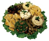 Mediterranean Platter  Hummos, babaganouj, taboulleh, vegetarian-stuffed grape leaves, spinach pie, feta cheese chunks, kalamata olives and pita bread.