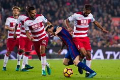 Lionel Messi (2nd R) of FC Barcelona fights for the ball with Mehdi Carcela-Gonzalez (R) and Matthieu Saunier (3rd R) of Granada CF during the La Liga match between FC Barcelona and Granada CF at Camp Nou stadium on October 29, 2016 in Barcelona, Catalonia.
