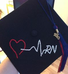 RN graduation cap - Created this by tracing image on the hat with a white colored pencil.  Then glued rhinestones over the pencil lines.  Really simple project, took less then 45 minutes.
