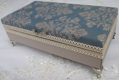 Caixa em MDF revestida com tecido 100%algodão. Detalhes em renda importada, puxador em metal e pezinhos em metal na cor prata. A peça na sua parte interior é flocada em preto (camurça) e possui 8 divisórias. Peça impermeabilizada na sua parte superior (tampa).