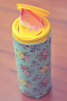 Recycled plastic bag dispenser - Take an old wipes container, make it pretty with fabric and Mod Podge, then stuff those plastic bags down inside!