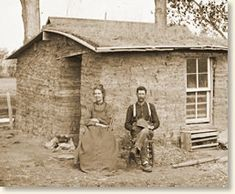A homesteader couple poses proudly in front of their sod home.