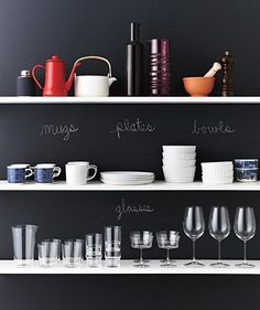 Short on cupboards? Get things out in the open and display dishes against a well-marked chalkboard wall.