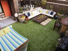 Designer Meg Caswell creates an urban outdoor oasis with a comfy sectional, a Tiki bar, an Indian oxcart turned coffee table and synthetic grass that will stay green all year long.