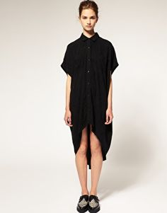 Black oversize shirt dress with dipped hem.
