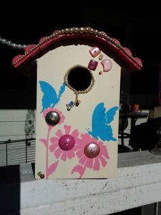 a bird house on sale at dollar general and some broken jewelry make a pretty birdhouse.