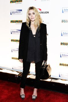 Ashley Olsen wears a silk button-down blouse, blazer, skinny jeans, embellished pumps, and a black duffle handbag