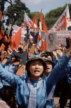 South Vietnam.  Female North Vietnamese troops enter Saigon carrying wooden rifles, red flags, and portrait of Ho Chi Minh, Apr. 1975 // by © Jacques Pavlovsky/Sygma/CORBIS