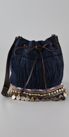"Elliot Mann Your Bag. This pleated canvas bucket bag features antiqued coin charms, beading, and braid details at the bottom. Adjustable leather shoulder strap and leather drawstring closure. Lined interior features zip pocket and patch pocket. * 11""H x 10""L x 5""D. * 24"" strap drop."
