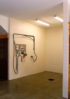 Wash stall with overhead hose hanger. Vaskeplads skal være mod sadelrum og på den væg skal der være bred vask og skabe over.