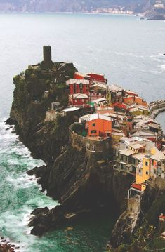 Hues of orange cottages line the coast of Cinque Terre in Italy.