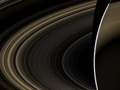 A splendid image from the Cassini spacecraft peering over the shoulder of Saturn, through its rings, and across interplanetary space back toward the inner solar system. The tiny white dot behind the faint inner rings - just above and to the right of the image center - is the bright, cloudy, but distant terrestrial planet Venus.